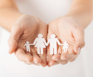 close up of womans cupped hands showing paper man family